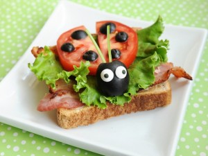Bacon Lettuce and Tomato BLT sandwich open-faced with tomatoes and olives cut to look like a ladybug on top of the leaf of lettuce