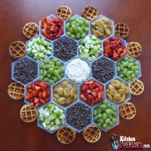Settlers of Catan gaming board food setup with grapes, chocolate chips, apples, strawberries, and bananas as toppings to miniature homemade waffles