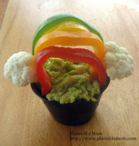 Spinach Artichoke Hummus in a green, yellow, orange, red pepper rainbow arch with cauliflower clouds for St. Patrick's day.