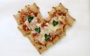 A heart shaped pizza made out of Totino's pizza rolls and spinach